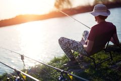 Młodego człowieka połów na jeziorze przy zmierzchem cieszy się hobby Zdjęcia Royalty Free