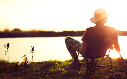 Młodego człowieka połów na jeziorze przy zmierzchem cieszy się hobby Zdjęcia Stock