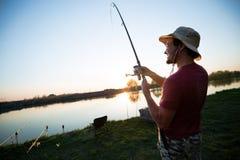 Młodego człowieka połów na jeziorze przy zmierzchem i cieszyć się hobby Zdjęcia Royalty Free
