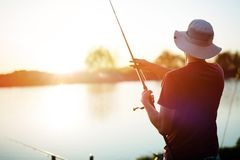Młodego człowieka połów na jeziorze przy zmierzchem i cieszyć się hobby Zdjęcie Royalty Free