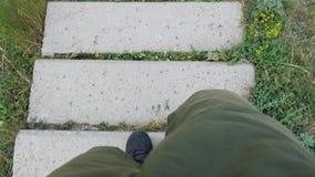 Młodego człowieka podróżnik w zieleni spodniach i czarnych butach wolno iść puszek i wtedy biega wzdłuż schodków z betonowymi pro zdjęcie wideo