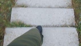 Młodego człowieka podróżnik w zieleni spodniach i czarnych butach wolno iść puszek i wtedy biega wzdłuż schodków z betonowymi pro zbiory wideo