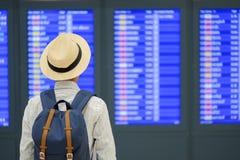 Młodego człowieka podróżnik z kapeluszowym sprawdza lota czasem, Azjatycki pasażerski patrzeć informacji deska w lotniska międzyn zdjęcia stock