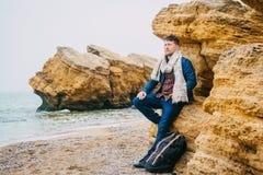 Młodego człowieka podróżnik z plecak pozycją na skale przeciw pięknemu morzu z falami, elegancki modniś chłopiec pozować zdjęcia royalty free