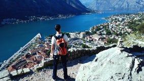 Młodego człowieka podróżnik z pomarańczowym plecakiem cieszy się widok Bok zatoka Obrazy Stock