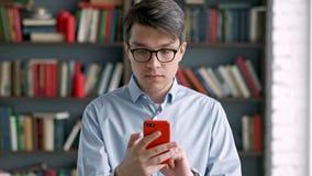 Młodego człowieka portret używać smartphone roześmianą pozycję w biblioteczny ogólnospołeczny medialny śmiesznym zbiory wideo