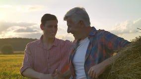 Młodego człowieka powitania stary rolnik i chwianie jego ręka, iść daleko od na słomy polu podczas zmierzchu wewnątrz, piękny kra zbiory