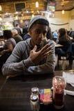 Młodego człowieka pozy podczas gdy czeka jego jedzenie w Miasto Nowy Jork Obrazy Stock