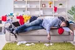 Młodego człowieka pracujący studiowanie w upaćkanym pokoju Zdjęcie Stock
