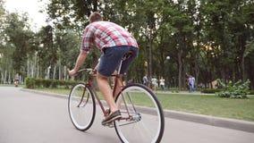 Młodego człowieka rocznika jeździecki bicykl przy parkową aleją Sporty faceta jeździć na rowerze plenerowy Zdrowy aktywny styl ży zbiory wideo