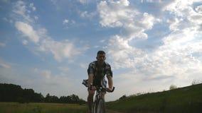 Młodego człowieka rocznika jeździecki bicykl przy wiejską drogą nad polem Sporty faceta kolarstwo wzdłuż kraju śladu plenerowego  Obrazy Stock
