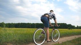 Młodego człowieka rocznika jeździecki bicykl przy wiejską drogą nad polem Sporty faceta kolarstwo wzdłuż kraju śladu plenerowego  Obrazy Royalty Free