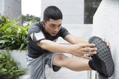 Młodego Człowieka rozciągania nogi fotografia stock