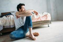 Młodego człowieka siedzący puszek na podłoga blisko przyglądającego outside i łóżka Zdjęcia Royalty Free