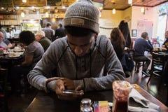 Młodego człowieka spojrzenia przy jego dzwonią podczas gdy czekający jego posiłek Obrazy Royalty Free