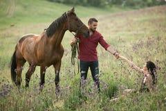 Młodego człowieka stojaki obok konia i trzymają za jego ręce kobieta zdjęcie royalty free