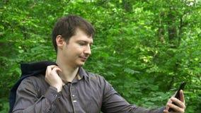 Młodego człowieka stojaki w drewnach, rzuty kurtka nad jego ramieniem i robią selfie swobodny ruch zdjęcie wideo