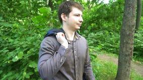 Młodego człowieka stojaki w drewnach, rzuty kurtka nad jego ramieniem swobodny ruch zbiory