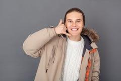Młodego człowieka studio odizolowywający na popielatego zima stylu kamery seansu wezwania przyglądającym gescie fotografia stock