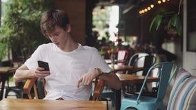 Młodego Człowieka surfingu internet w telefonie komórkowym, przydatnym dotyku i dosłanie wiadomości tekstowej w kawiarni, Przysto zbiory