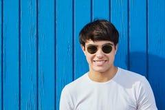 Młodego człowieka szczęśliwy mężczyzna w okularach przeciwsłonecznych przeciw błękitnej drewnianej ścianie Zdjęcia Royalty Free