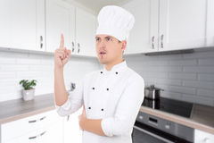 Młodego człowieka szef kuchni z doskonałym pomysłem w nowożytnej kuchni zdjęcia royalty free