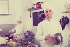 Młodego człowieka szefa kuchni kulinarny jedzenie przy kuchnią Obraz Stock
