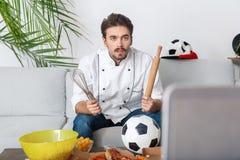 Młodego człowieka szefa kuchni wielbiciela sportu dopatrywania dopasowanie patrzeje ekran koncentrującego obraz stock