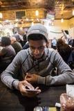 Młodego człowieka teksty podczas gdy czeka jego jedzenie przy lokalnym gościem restauracji Zdjęcie Stock