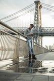 Młodego człowieka teksty przed Miasto Nowy Jork ` s Williamsburg mostem Zdjęcie Stock