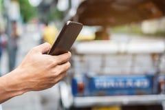 Młodego człowieka turysta lub przypadkowego biznesmena rozkazuje taxi przez taksówki zastosowania na smartphone w miasto ulicie,  zdjęcia stock