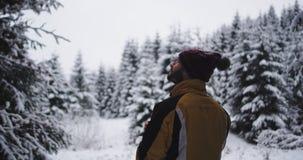 Młodego człowieka turystyczny podróżować samotnie w ciężkim zima dniu zatrzymywał po środku śnieżnego lasu i bierze niektóre gorą zbiory wideo