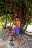 Młodego człowieka ubijanie kava zakorzenia w Lavena wiosce, Taveuni wyspa, zdjęcie stock