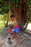 Młodego człowieka ubijanie kava zakorzenia w Lavena wiosce, Taveuni wyspa, zdjęcia stock