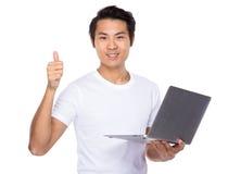 Młodego człowieka use notebook i kciuk up Obrazy Stock