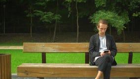 Młodego człowieka use smartphone i odpoczynek w parku zbiory