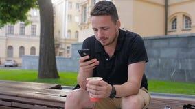 Młodego człowieka use telefonu obsiadanie na ławce pije kawowego outside w mieście zbiory