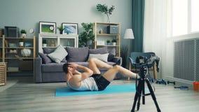 Młodego człowieka vlogger magnetofonowy wideo opowiada brzusznych mięśnie i ćwiczy zbiory wideo