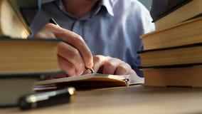 Młodego człowieka writing w notatce na stole z stosami książki Wiedza i mądrości pojęcie zbiory