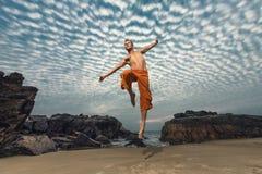 Młodego człowieka wysoki doskakiwanie na plaży Zdjęcia Royalty Free