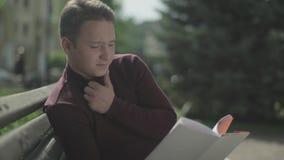 Młodego człowieka zamyślenie czyta książkę w parku zbiory wideo