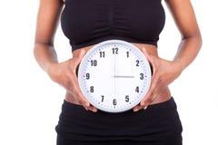 Młodego czarnego afrykanina amerykańska kobieta trzyma zegar przed h Zdjęcia Stock