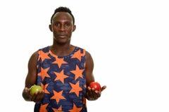 Młodego czarnego afrykanina mężczyzna mienia zielony i czerwony jabłko Obraz Royalty Free