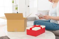 Młodego eleganckiej kobiety otwarcia pakuneczka doręczeniowy pudełko Zdjęcie Stock