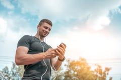 Młodego facet atlety mężczyzny szczęśliwy ono uśmiecha się, trzymający telefon w jego rękach, słucha muzyka z hełmofonami Lato w  zdjęcia royalty free