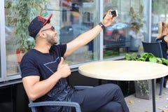 Młodego faceta arabski męski mężczyzna robi selfie, opowiada na Skype, uśmiechy i Zdjęcie Stock