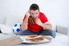 Młodego fan mężczyzna dopatrywania mecz futbolowy na tv jest ubranym drużynowego bydła cierpienie nerwowego i stres Zdjęcie Royalty Free