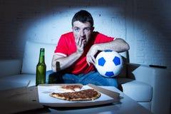 Młodego fan mężczyzna dopatrywania mecz futbolowy na tv w drużynowego bydła cierpieniu nerwowym i stresie Zdjęcie Royalty Free