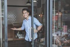Młodego fryzjera męskiego biegły uśmiechnięty powitalny klient jego zakład fryzjerski Zdjęcia Stock