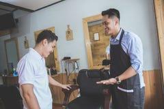 Młodego fryzjera męskiego biegły uśmiechnięty powitalny klient jego zakład fryzjerski Obrazy Stock